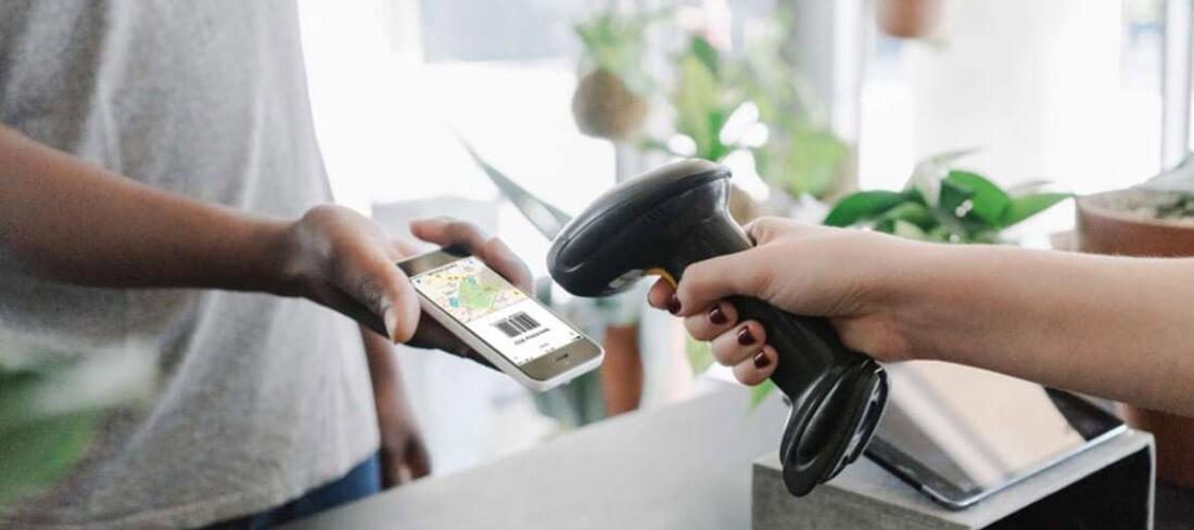 Eine Hand hält ein Smartphone mit Code zum Bargeldabheben vor einen Scanner einer Supermarktkasse.